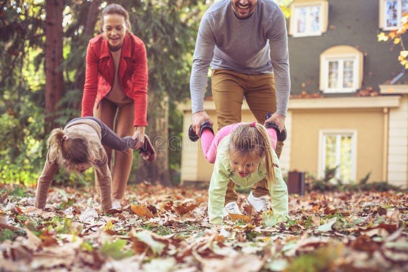 Elternhilfstöchter, die auf Hände gehen playful In Bewegung lizenzfreie stockfotos