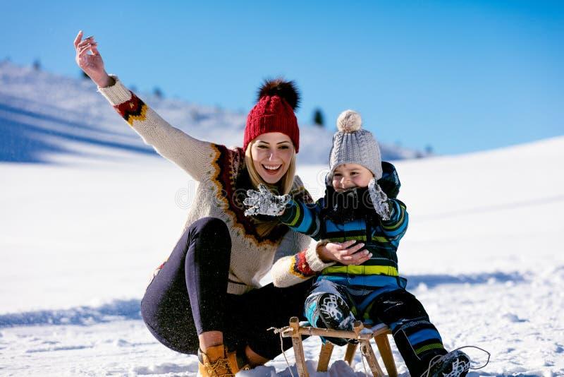 Elternschaft, Mode, Jahreszeit und Leutekonzept - glückliche Familie mit dem Kind auf Schlitten draußen gehend in Winter stockfotos