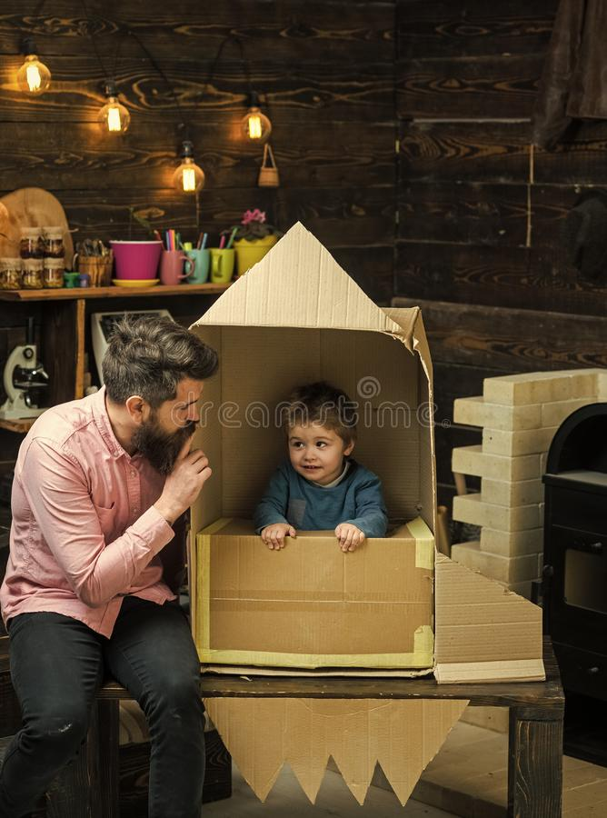 Elternschaftskonzept Jungenspiel mit Vati, Vater, kleiner Kosmonaut sitzen in der Rakete, die aus Pappschachtel heraus hergestell lizenzfreies stockfoto