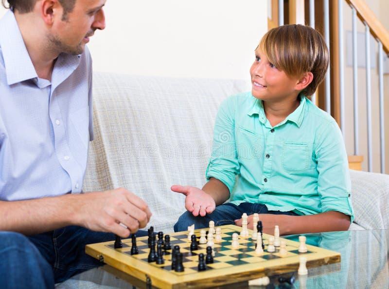 Elternteil, das seinen Sohn spielt Schach unterrichtet stockfotografie
