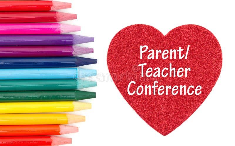 Elternteil-Lehrer-Conference-Mitteilung auf rotem Herzen mit farbigen Aquarellbleistiften stockbild