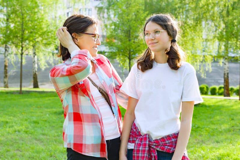 Elternteil und Jugendlicher, Mutter spricht mit ihrer jugendlich Tochter 13, 14 Jahre alt Hintergrundnatur, Park stockbild
