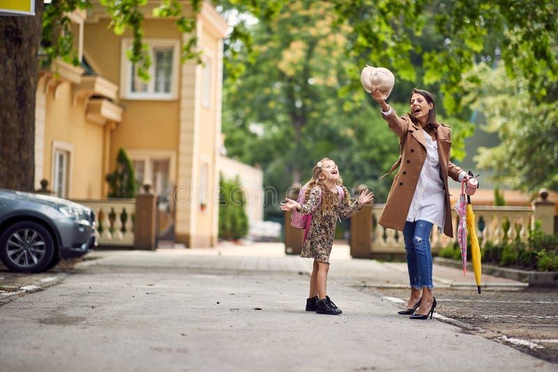 Elternteil und Schüler der Grundschule Frau und Mädchen mit Rucksack Anfang von Lektionen Erster Tag des Falles lizenzfreie stockfotos