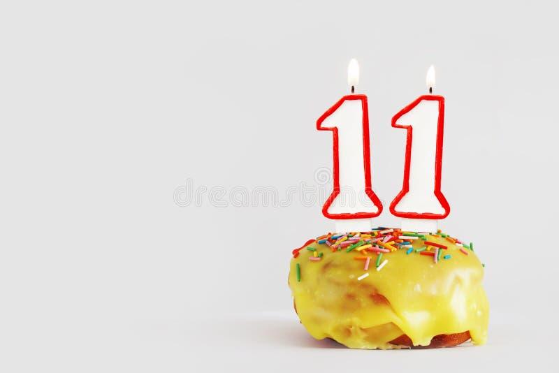 Elva år årsdag Födelsedagmuffin med vita brinnande stearinljus med den röda gränsen i form av nummer elva fotografering för bildbyråer