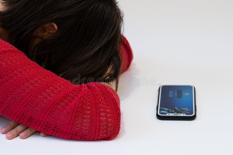 Elva, Estland 15 november 2018 meisje leunt op wapens die het gezicht verbergen, telefoon met online Fortnite game Epic games log royalty-vrije stock afbeeldingen