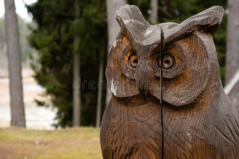 Elva Estonia 04.05.2018 close up of owl bird sculpture carved from wood in forest.  stock image