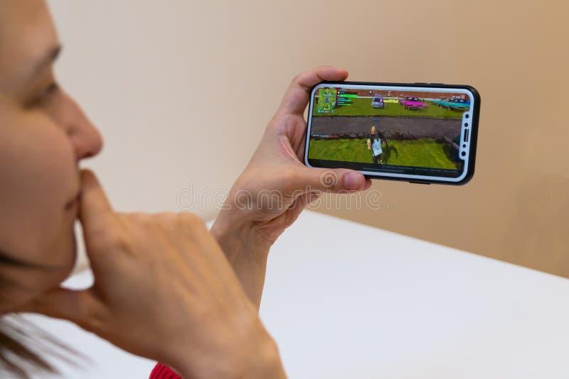 Elva, Estonia - 15 de noviembre de 2018: iphone de la tenencia de la muchacha con el juego en línea de Fortnite en la exhibición, foto de archivo