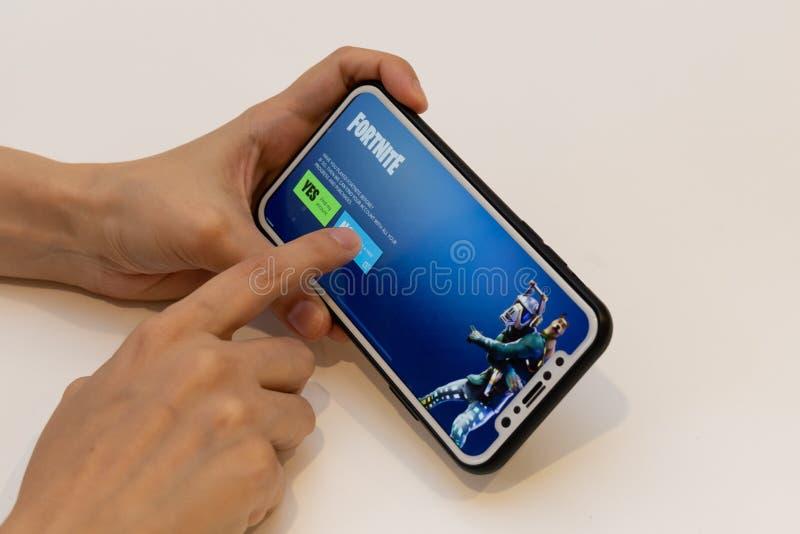 Elva, Estonia 15 listopada 2018, dziewczyna trzymająca telefon z grą online Fortnite Epic, naciskając przycisk obraz royalty free