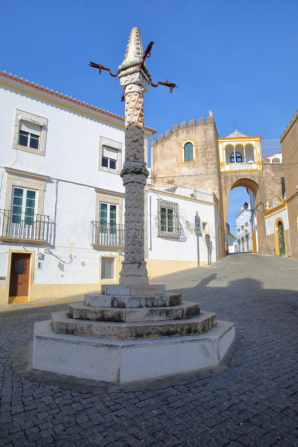 ELVAS PORTUGAL: Largo de Santa Clara Square med en ställa vid skampålen i förgrunden arkivbild