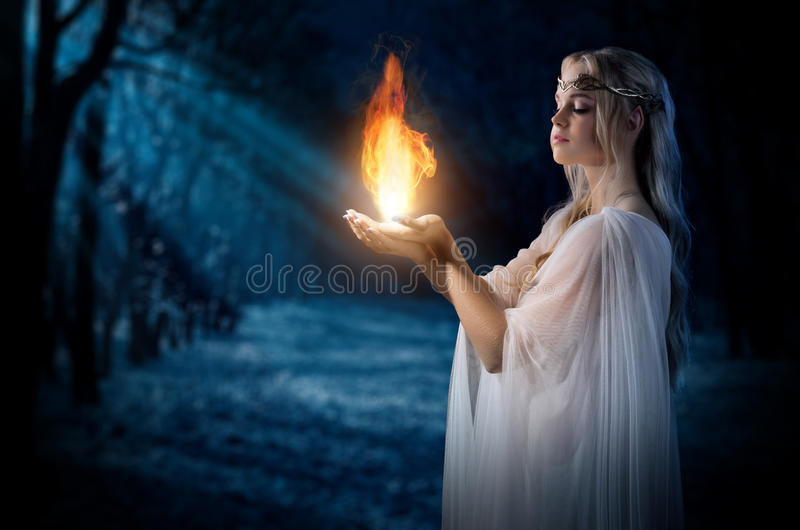 Elven girl holding fire in palms at night forest. Young elven girl holding fire in palms at night forest royalty free stock images