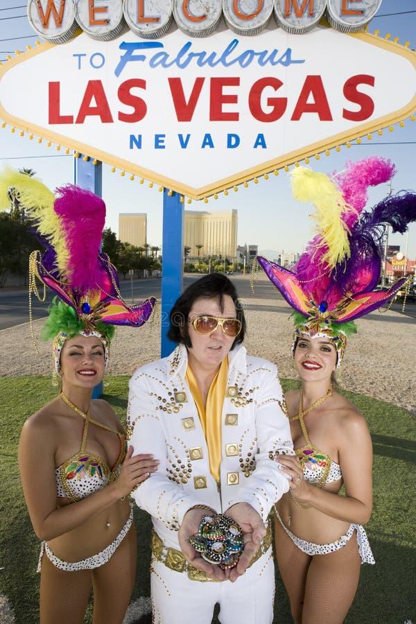 Elvis Presley Impersonator Holding Chips And che sta con i ballerini del casinò immagini stock libere da diritti