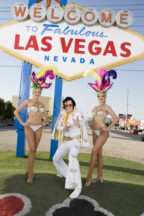 Elvis Presley Impersonator Standing With Casino Dancers. Portrait of Elvis Presley impersonator standing with casino dancers against sign board royalty free stock image