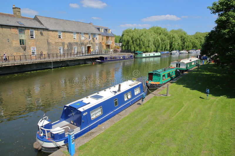 ELY, UK - MAY 26, 2017: The riverside in Spring with moored barges on the Great Ouse river and traditional houses royalty free stock images