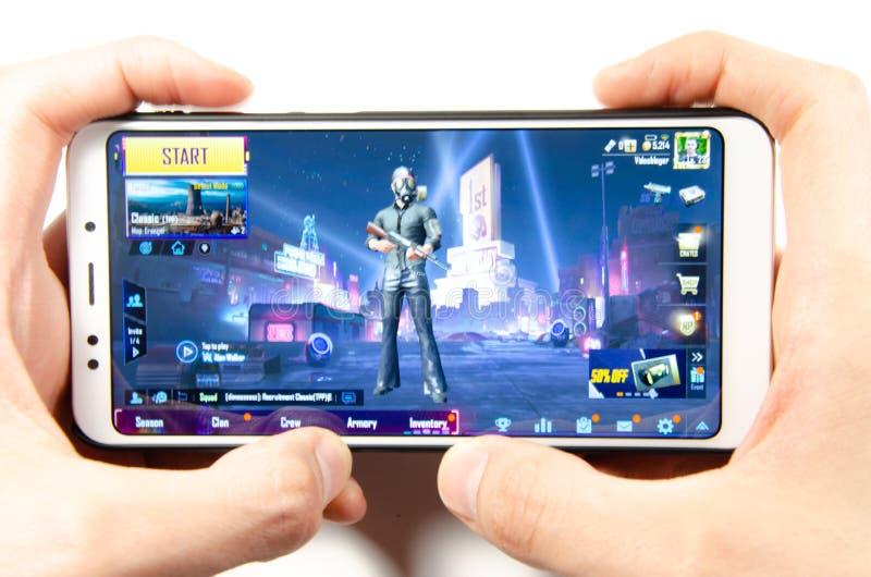 Em abril de 2019 Kramatorsk, Ucr?nia O gameplay do m?bil do jogo PUBG G em um smartphone branco imagens de stock