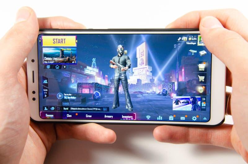 Em abril de 2019 Kramatorsk, Ucr?nia O gameplay do m?bil do jogo PUBG G em um smartphone branco foto de stock