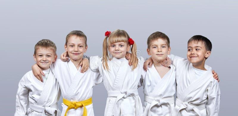 Em atletas pequenos de um fundo cinzento no karategi fotos de stock