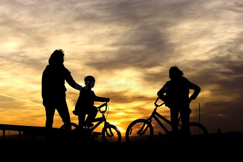 Em bicicletas no por do sol. fotografia de stock