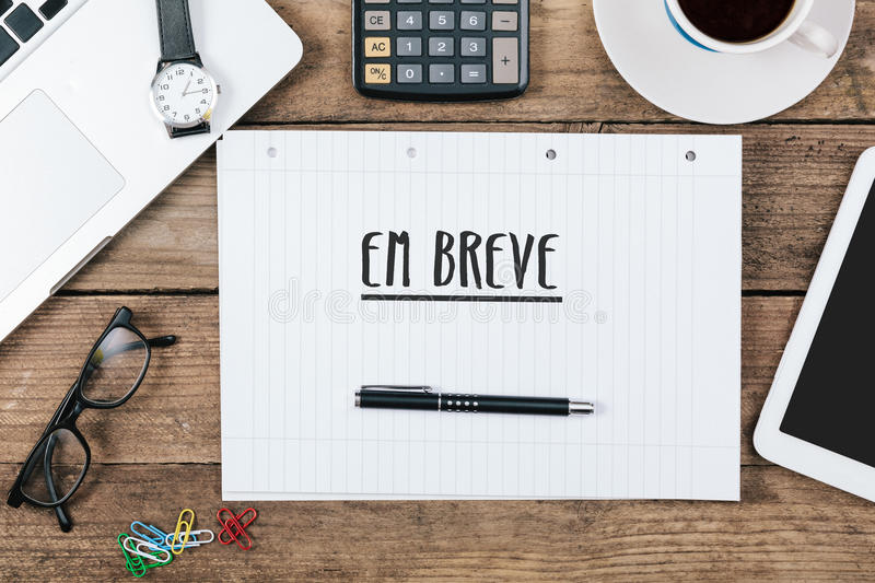 Em breve, Portuguese text for Coming Soon on note pad at office. Em breve, Portuguese text for Coming Soon, on note pad at office desk with electronic devices royalty free stock image
