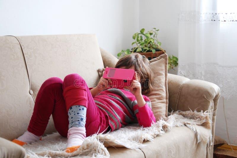 EM CASA: Uma menina com um móbil imagens de stock royalty free