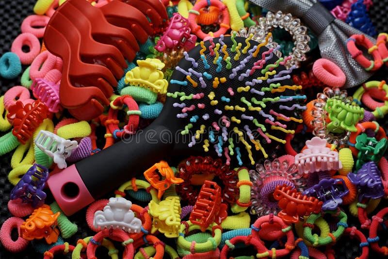 Em faixas elásticas coloridas multi-coloridas para o cabelo encontram-se um grampo do pente e de cabelo imagens de stock