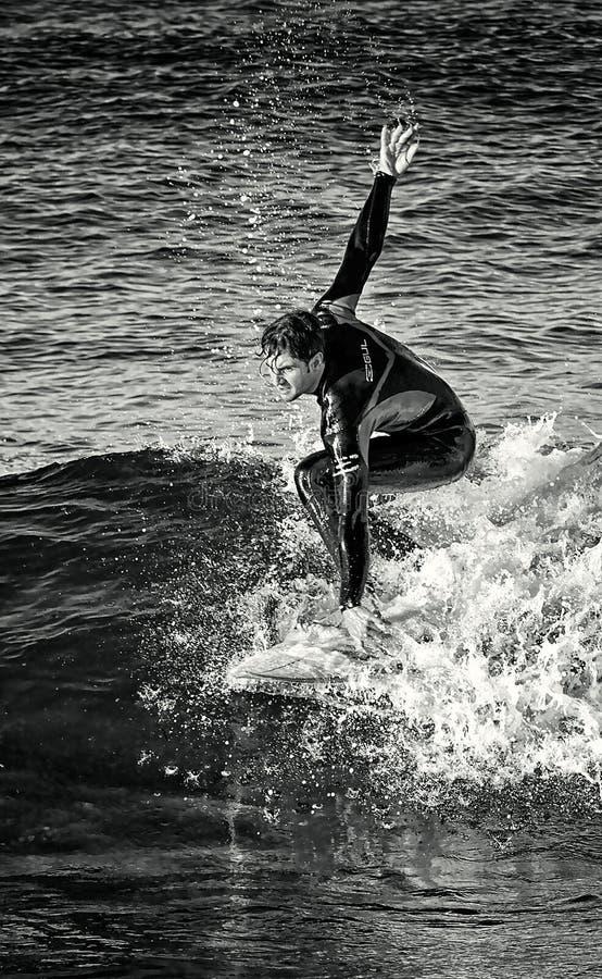 Em fevereiro de 2019 Surfista que monta uma onda apenas, pulverizador de mar, esportes de água, praia do mesquida de cala, mallor imagem de stock