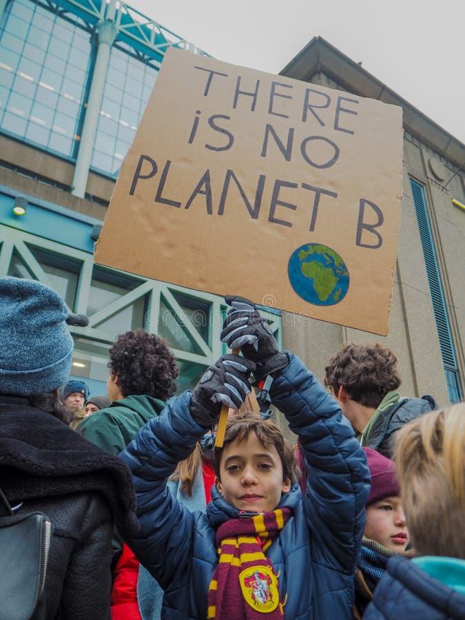 Em janeiro de 2019 - Bruxelas, Bélgica: menino novo com um cartaz feito a mão com slogan em uma marcha de protesto para alteraçõe imagens de stock