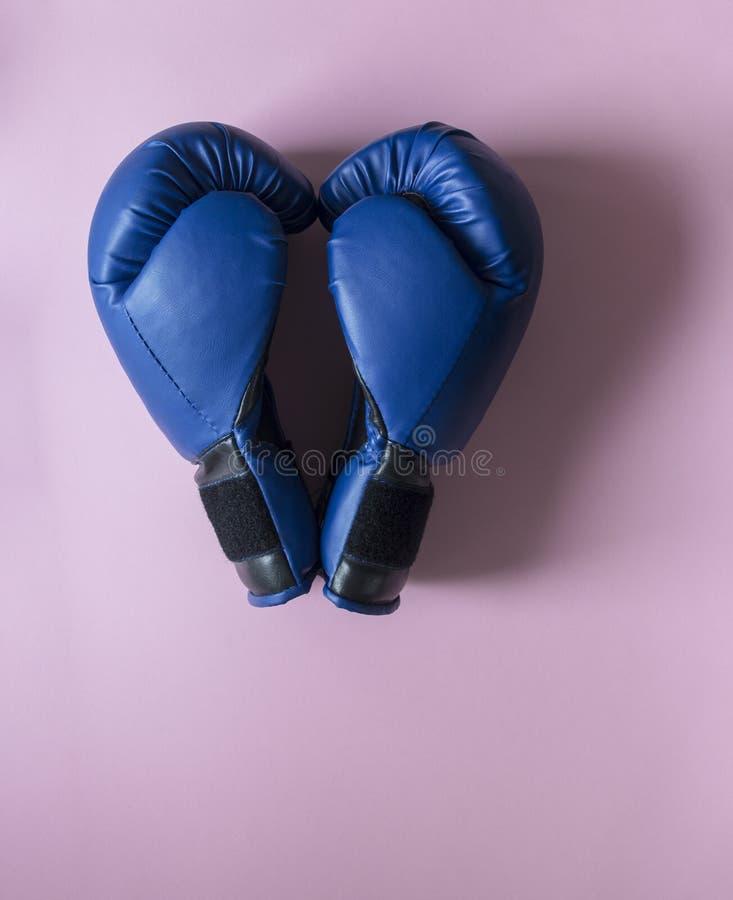 Em luvas de encaixotamento cor-de-rosa do fundo dois da cor azul na vista do coração fotografia de stock