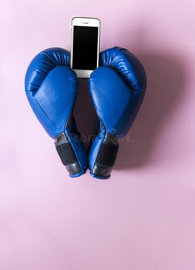 Em luvas de encaixotamento cor-de-rosa do fundo dois da cor azul sob a forma de um coração com um telefone nas mãos imagens de stock