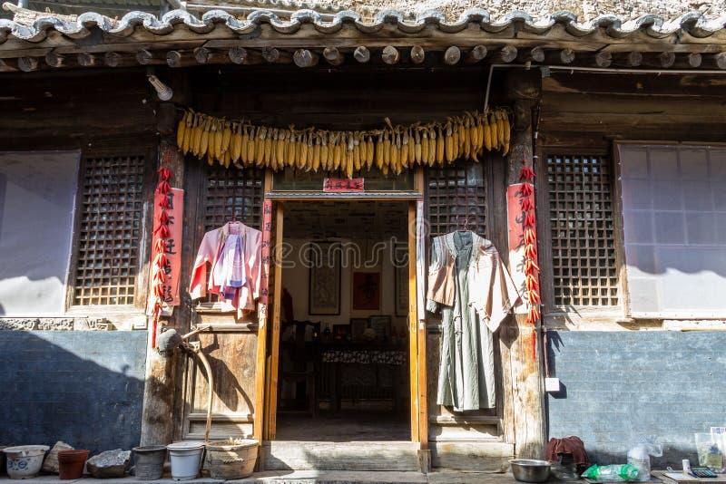 Em março de 2014, Chuandixia, Hebei, China: milho, roupa e pimenta vermelha pendurados para fora para secar na entrada de uma cas imagens de stock