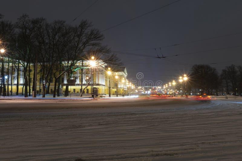 Em março de 2019, Rússia, St Petersburg A estrada à ponte do palácio Carros que passam pelo Admiralty Opinião da noite Exposição  fotos de stock royalty free