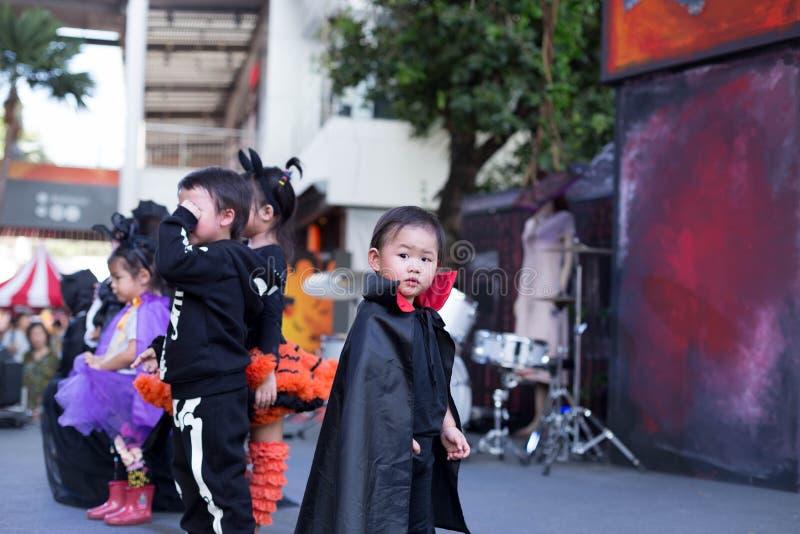 Em Na mega Banguecoque Tailândia do golpe: As crianças pequenas que vestem o Dia das Bruxas trajam o jogo na fase foto de stock