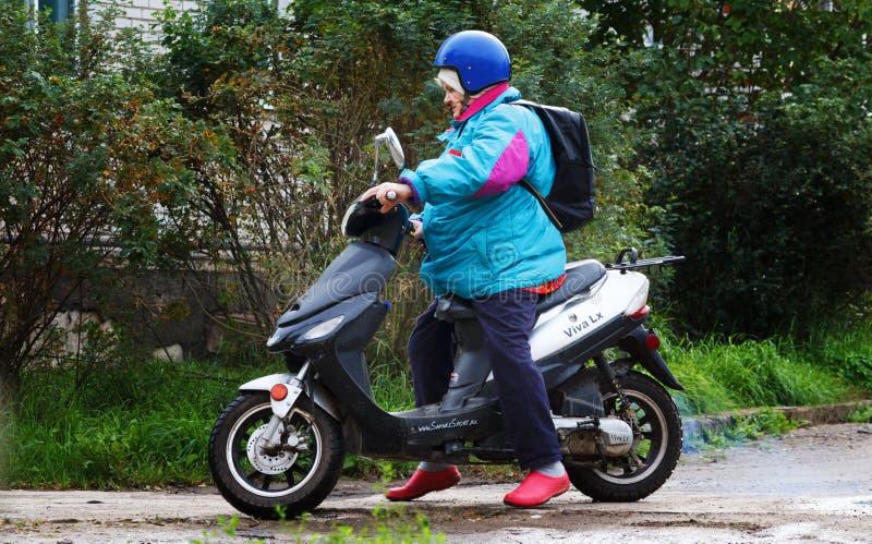Em novembro de 2018 Rússia St Petersburg, vila de Nazia, avó em uma bicicleta motorizada fotografia de stock