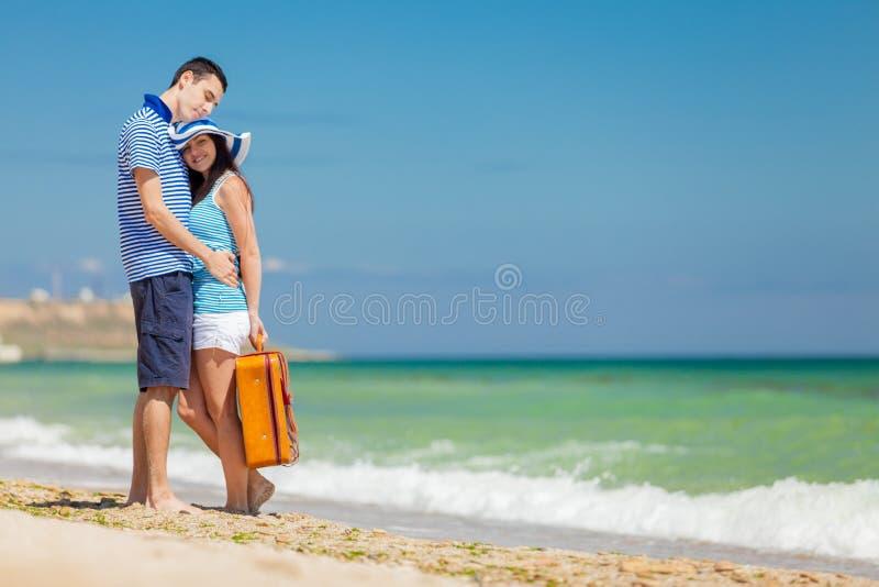 Em pares do amor na roupa azul com mala de viagem imagem de stock