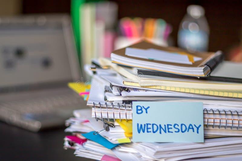 Em quarta-feira; Pilha de originais e de portátil na mesa de trabalho imagens de stock royalty free