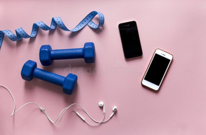 Em smartphones azuis de um telefone dois do centímetro da fita da cor dos pesos do fundo do rosa com preto branco dos fones de ou imagens de stock royalty free