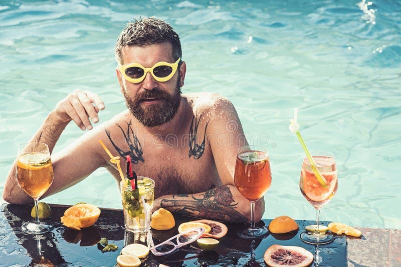Em topless nude do músculo do homem branco com bebida do cocktail na piscina no sentimento fresco imagens de stock