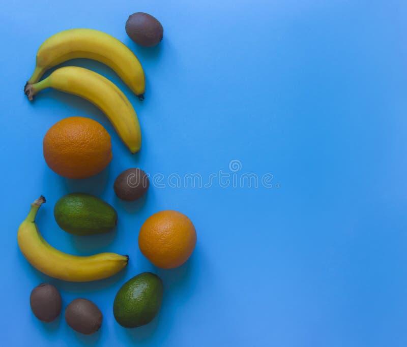 Em um fundo azul no quivi lateral do abacate das bananas das laranjas do fruto da mentira imagens de stock royalty free