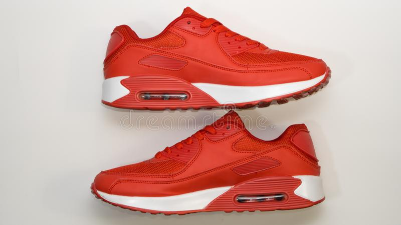 Em um fundo branco, close-up, sapatilhas vermelhas dos esportes, com sola branca, há uma sombra fotos de stock