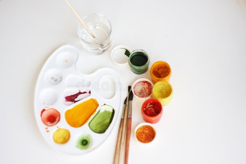 Em um fundo branco são as fontes da arte: pinturas do guache, uma paleta, escovas e um vidro com água foto de stock