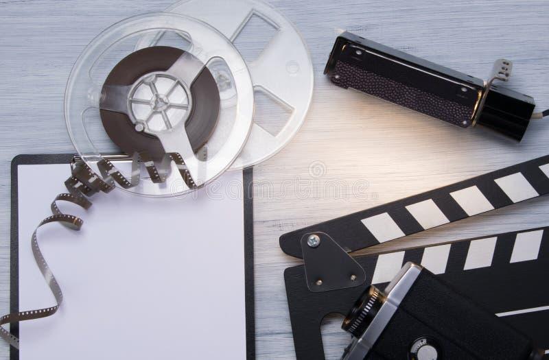 Em um fundo claro, o filme, câmara de vídeo velha, dobra para o tiro e um caderno limpo, com espaço para escrever fotografia de stock