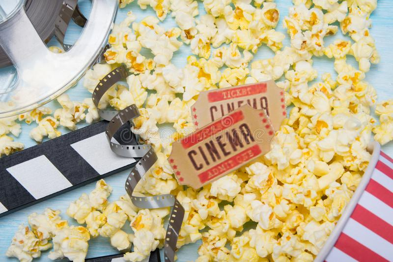 Em um fundo claro, a pipoca dispersada, dois bilhetes do filme, dobra para o película e o filme foto de stock royalty free