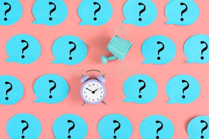 Em um fundo cor-de-rosa, muitas etiquetas azuis com pontos de interrogação são coladas Entre eles, um despertador e molhar azul imagem de stock royalty free