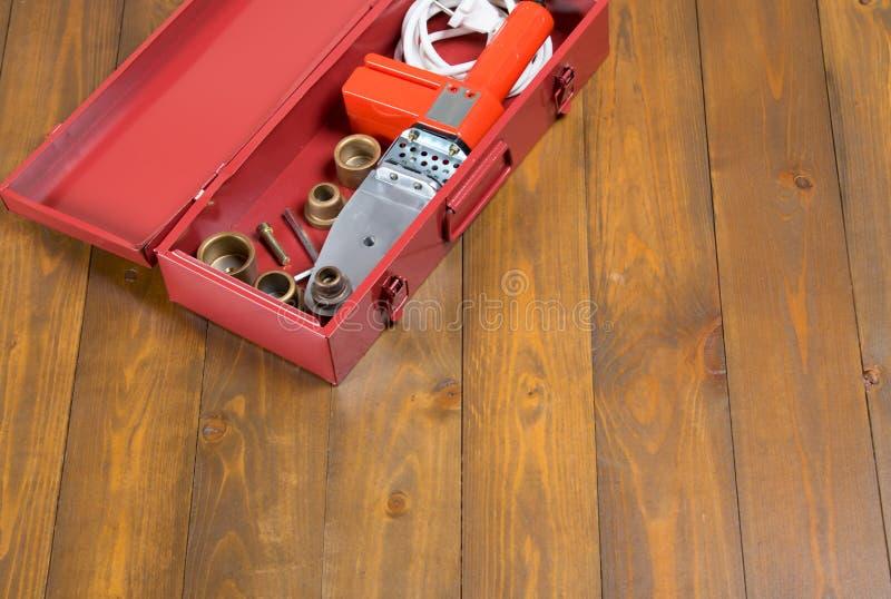 Em um fundo de madeira escuro, em uma caixa vermelha com um ferro de solda e um grupo de bocais para o reparo e na construção das foto de stock royalty free