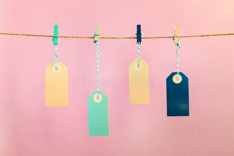 Em um fundo do rosa fotografado etiquetas Quatro etiquetas vazias coloridos penduram em uma corda fixada com pregadores de roupa fotografia de stock royalty free