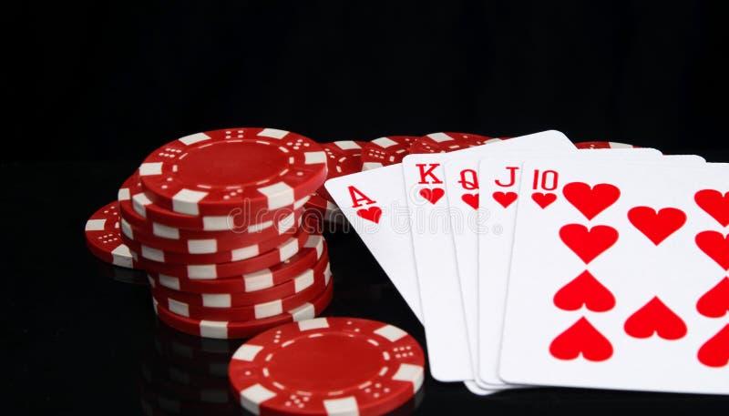 Em um fundo preto com reflexão, as microplaquetas vermelhas e uma mão de vencimento, no pôquer, close-up foto de stock