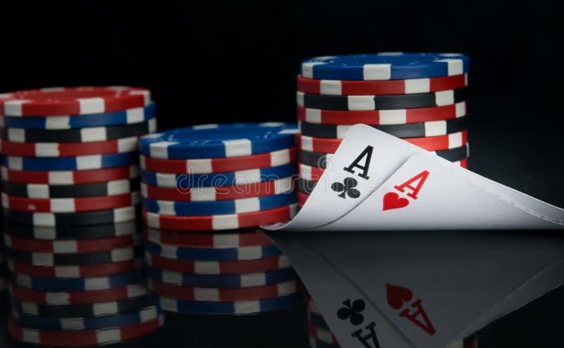 Em um fundo preto e em uma grande aposta das microplaquetas de cores diferentes, dois cartões de jogo, ACE, com reflexão, há um l imagem de stock