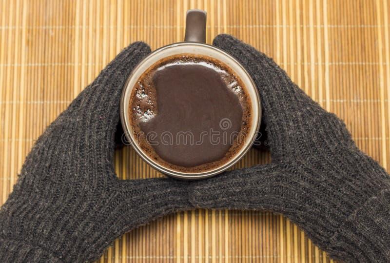 Em um guardanapo de madeira há uma caneca com cacau, que é mantido pelas mãos em luvas do inverno foto de stock