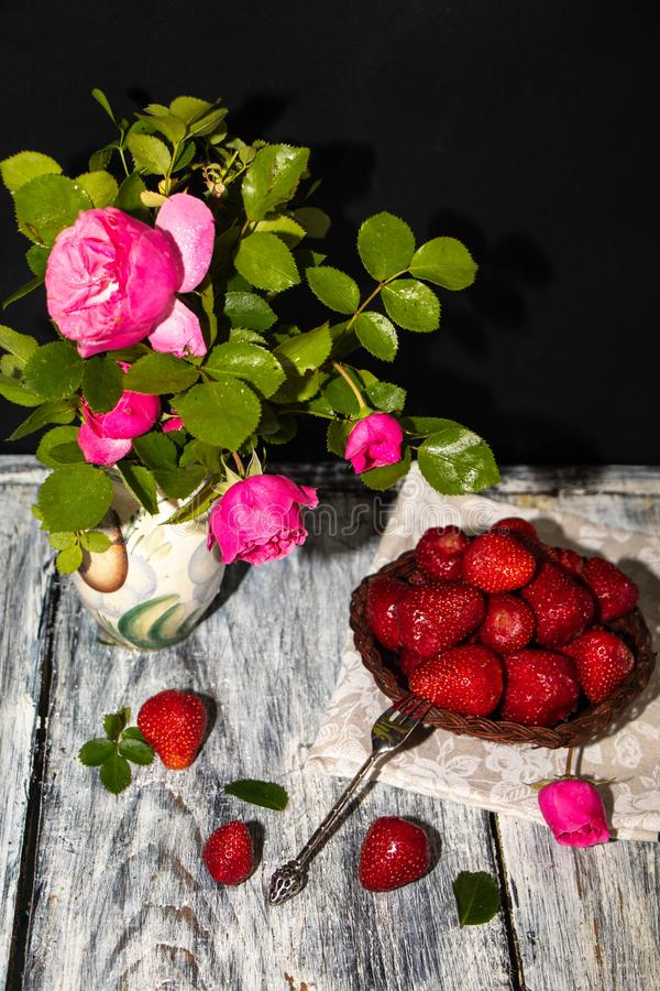 Em um jarro pintado há uns ramos de rosas lilás e de folhas do jasmim fotos de stock royalty free