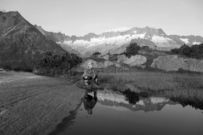 Em um lago da montanha a paisagem é refletida um caminhante faz uma ruptura fotos de stock