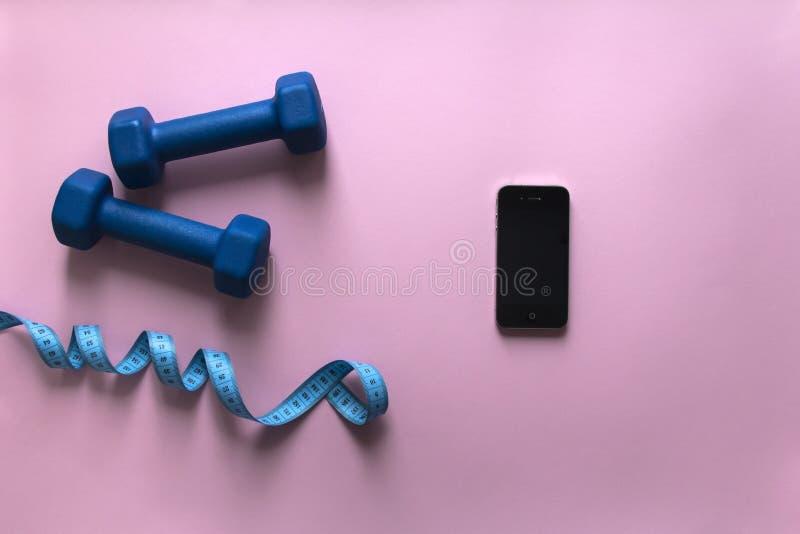 Em um smartphone azul do telefone do centímetro da fita da cor dos pesos do fundo do rosa foto de stock